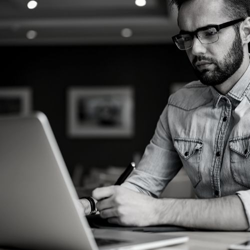 Man Taking Notes Next To Laptop